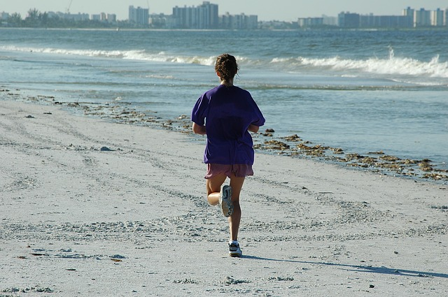 A woman jogging down the beach while trying to stay fit after moving to Florida.